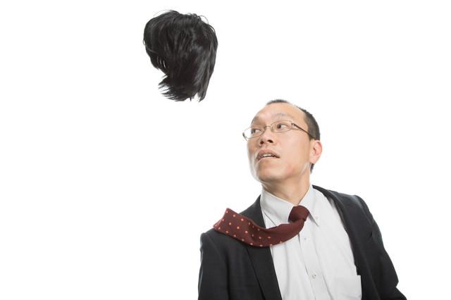 強風でカツラを飛ばされてしまった薄毛の男性会社員の写真