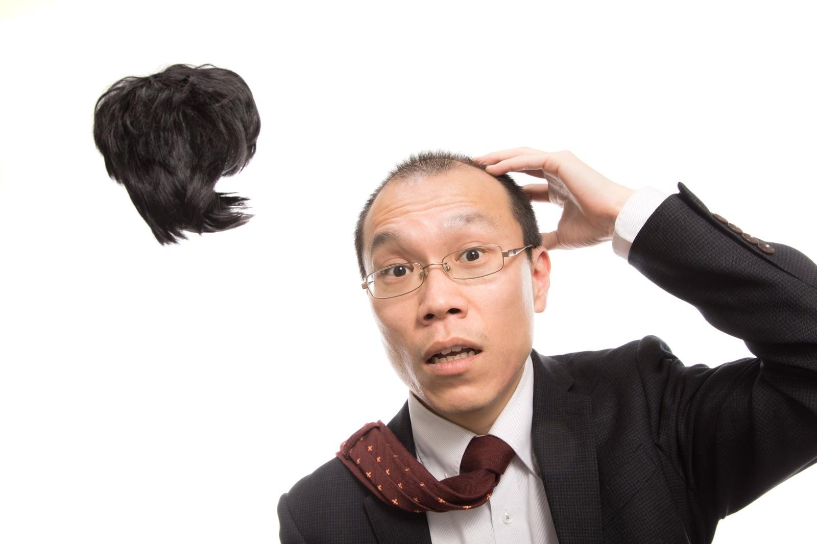 「強風でカツラが飛ばされ唖然とする男性会社員」の写真[モデル:サンライズ鈴木]