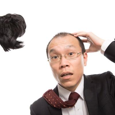 「強風でカツラが飛ばされ唖然とする男性会社員」の写真素材