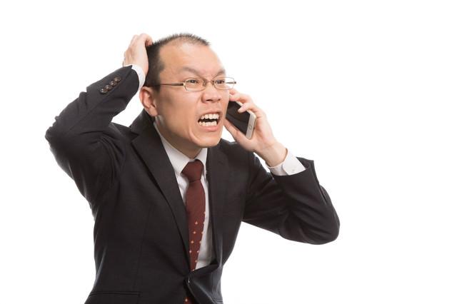 大失敗で電話越しに謝る薄毛の上司の写真