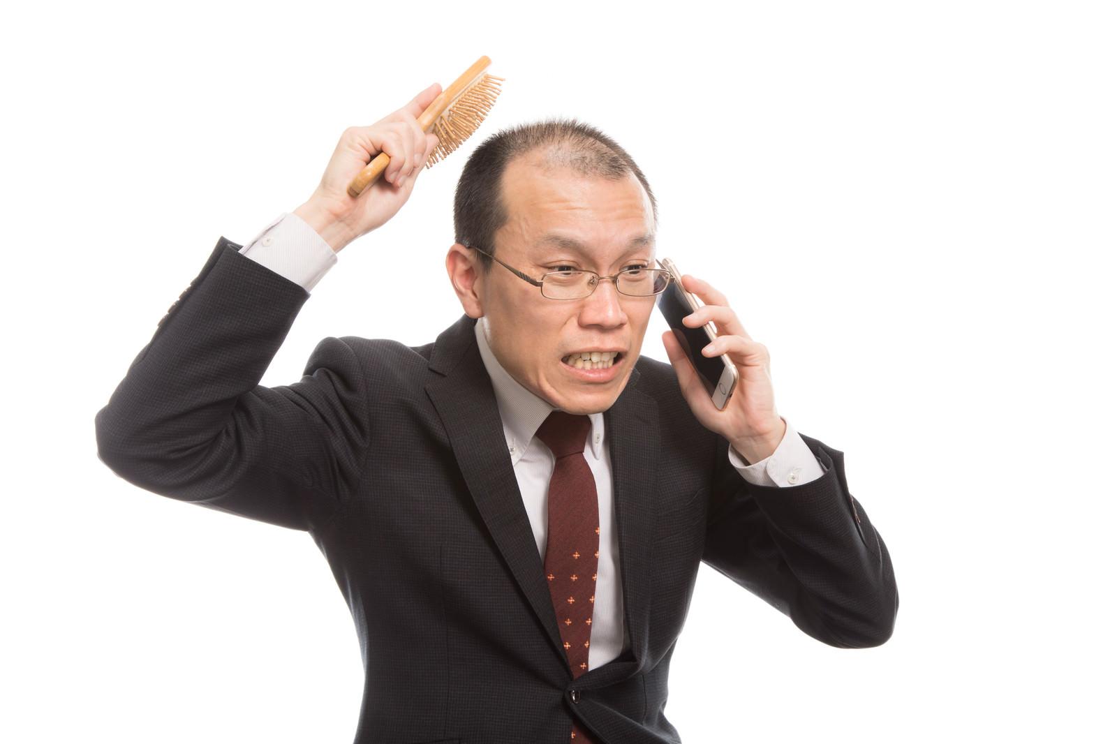 「頭頂部が薄い上司は育毛ブラシを使いながら電話する」の写真[モデル:サンライズ鈴木]