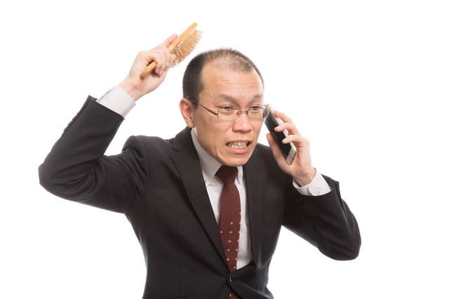 「頭頂部が薄い上司は育毛ブラシを使いながら電話する」のフリー写真素材