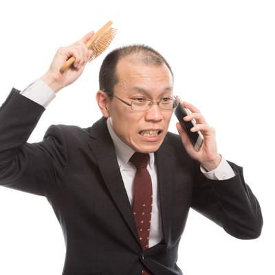 頭頂部が薄い上司は育毛ブラシを使いながら電話するの写真