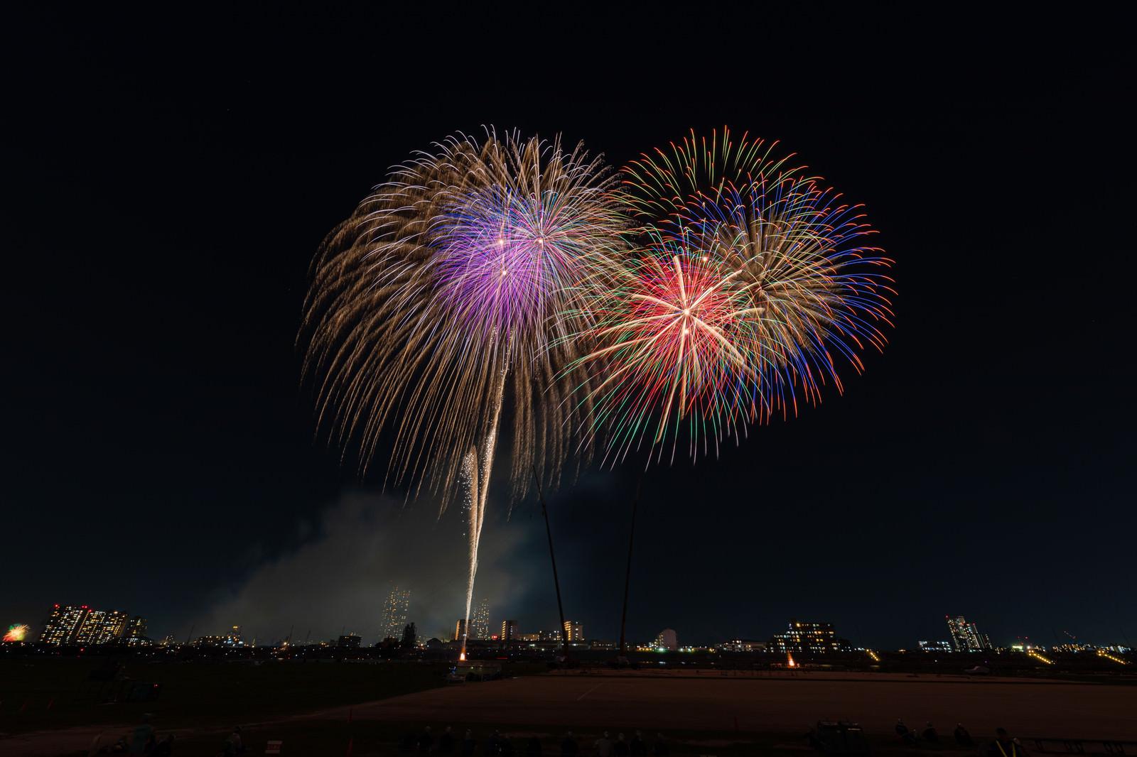 「河川敷から打ち上がる花火」の写真