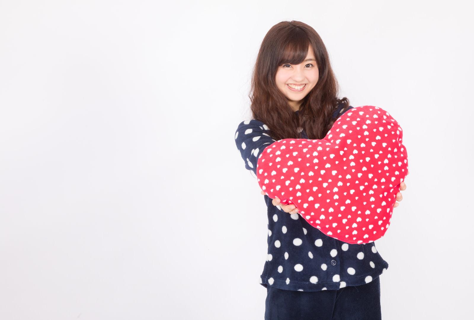 「ハートクッションを差し出すパジャマ女子 | ぱくたそフリー素材」の写真[モデル:河村友歌]