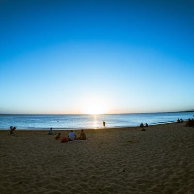 ハワイのサンセットを眺める人々の写真
