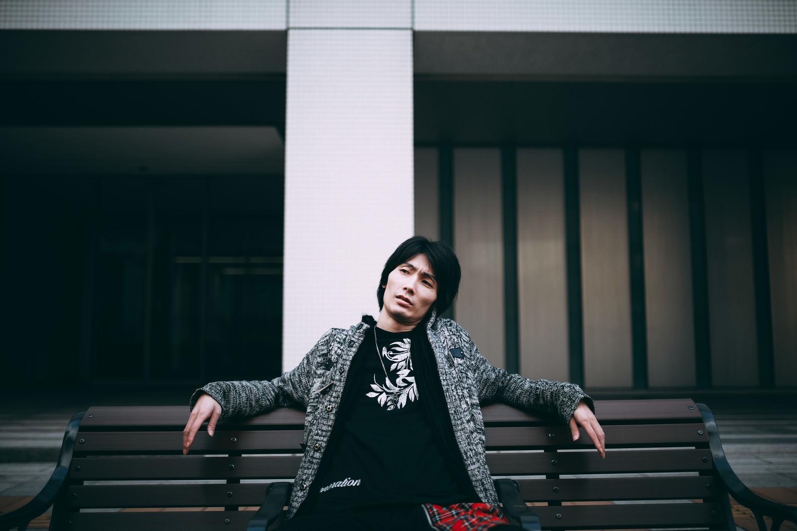 「ベンチで悪態をつく男性」の写真[モデル:ハヤト]