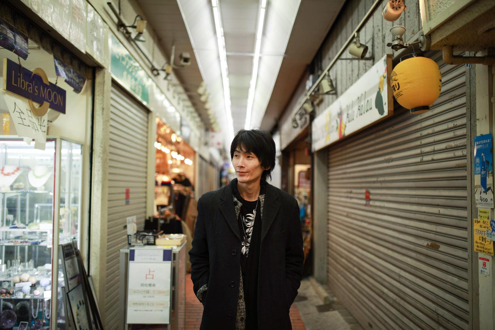 「商店街を歩く男性」の写真[モデル:ハヤト]