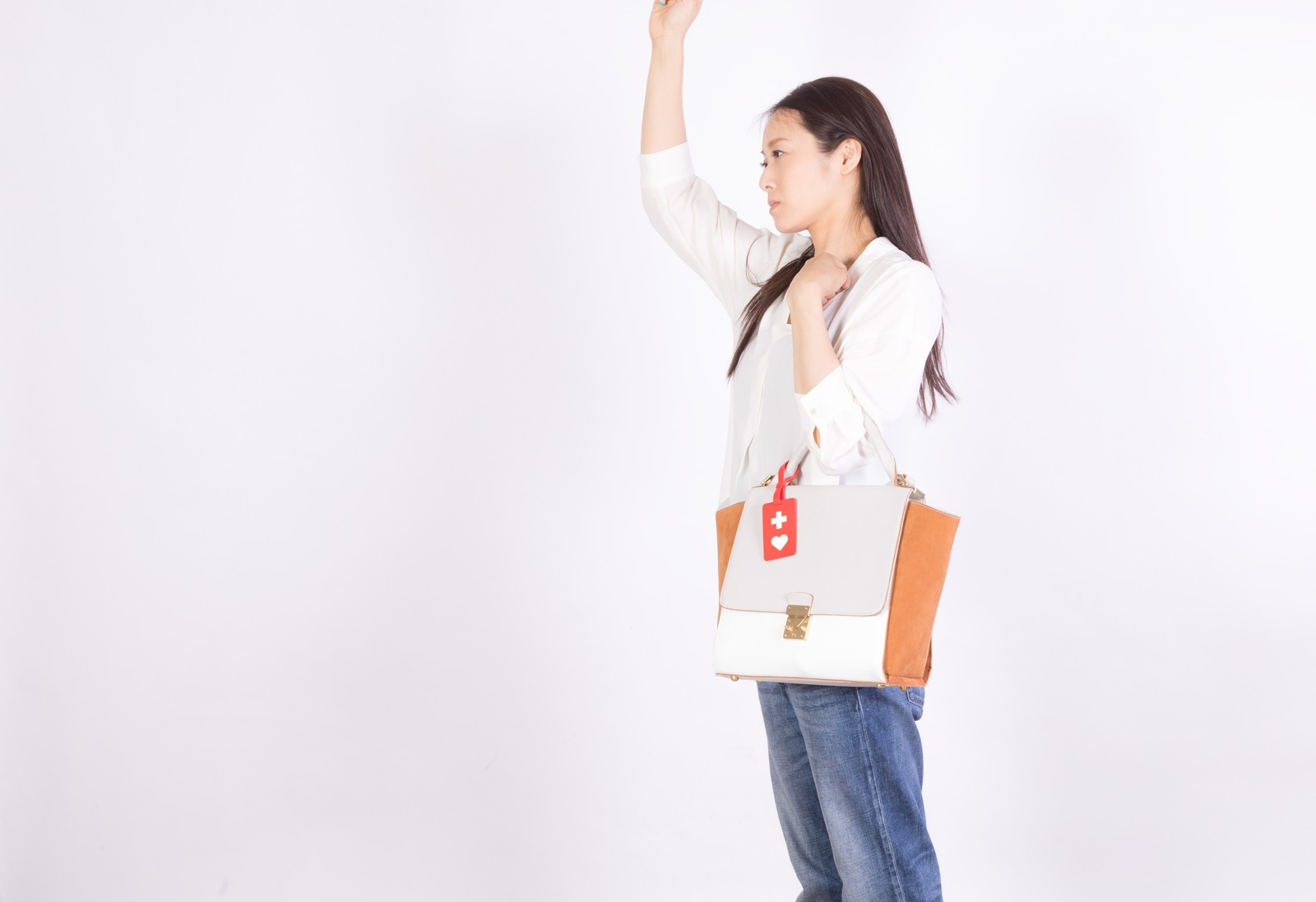 「吊革につかまるヘルプマーク所有者(女性)」の写真[モデル:土本寛子]