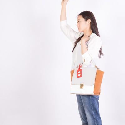 「吊革につかまるヘルプマーク所有者(女性)」の写真素材