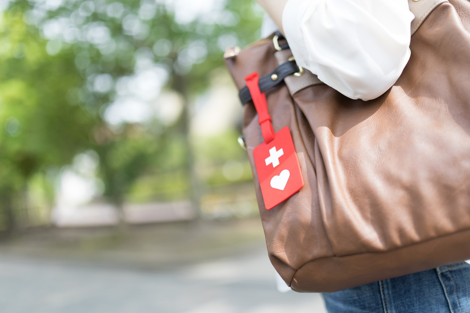 「十字とハートが付いた赤いマークの「ヘルプマーク」」の写真[モデル:土本寛子]
