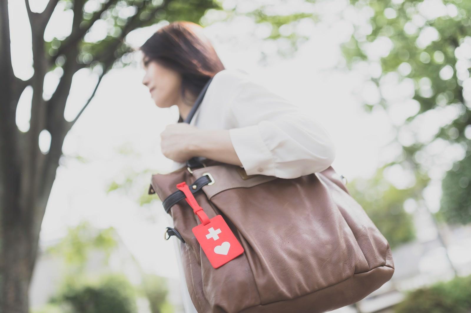 「ヘルプマークをバッグにつけて出社する女性」の写真[モデル:土本寛子]