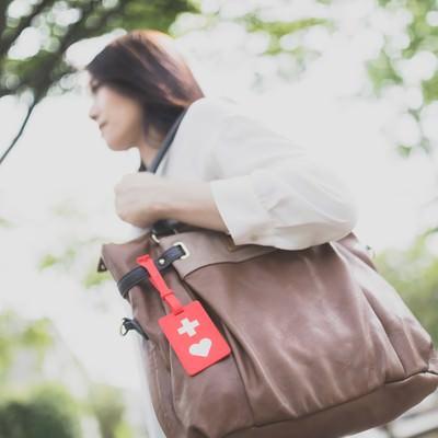 「ヘルプマークをバッグにつけて出社する女性」の写真素材