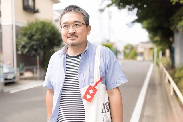 トートバッグにヘルプマークをつけて近所を歩く男性の写真