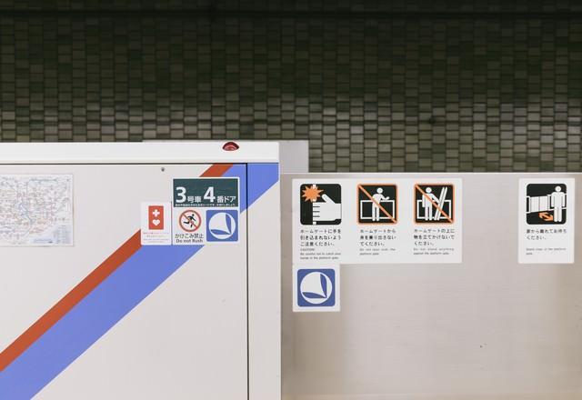 駅のホームドアに貼られたヘルプマークの表示の写真