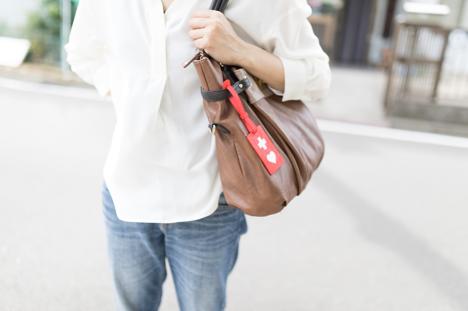 「バッグにヘルプマークをつけて外出する女性」の写真[モデル:土本寛子]
