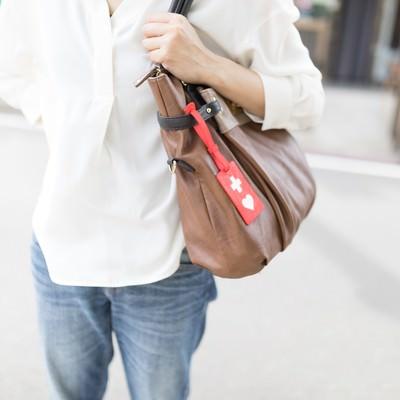 バッグにヘルプマークをつけて外出する女性の写真