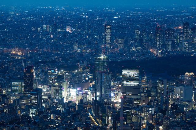 渋谷付近のビル群と空撮夜景の写真