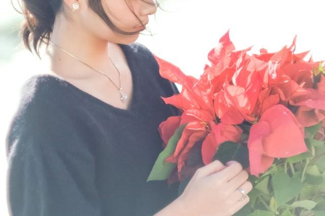 赤いポインセチアを持つ女性の写真