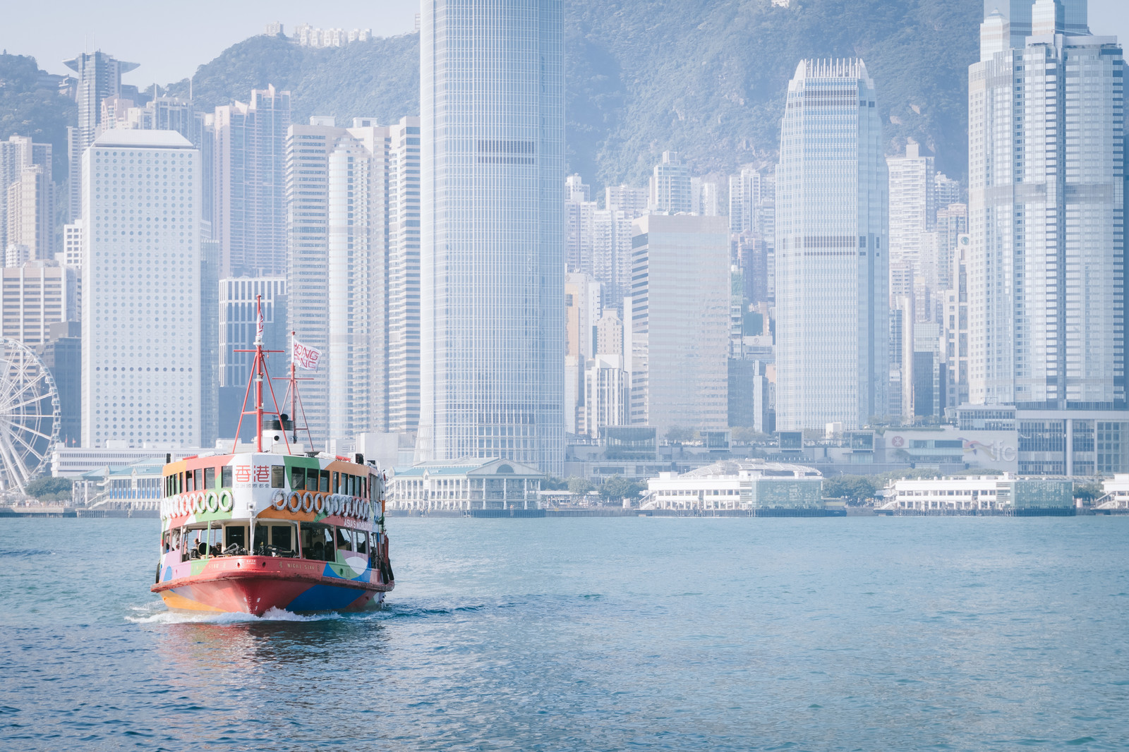 「香港のビル群と観光フェリー」の写真