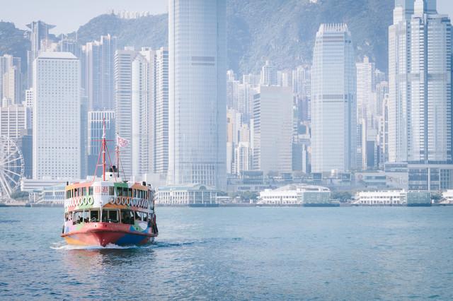 香港のビル群と観光フェリーの写真