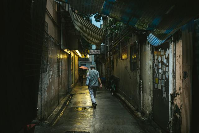 小雨が降る下町の路地裏と歩行者(香港)の写真
