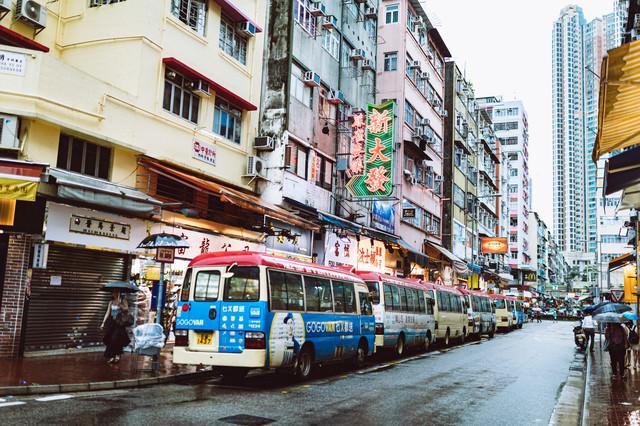 路駐するバスと雑多な街並み(香港)の写真