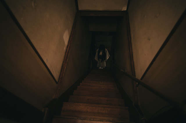 古民家の階段下に立つ女性の姿の写真