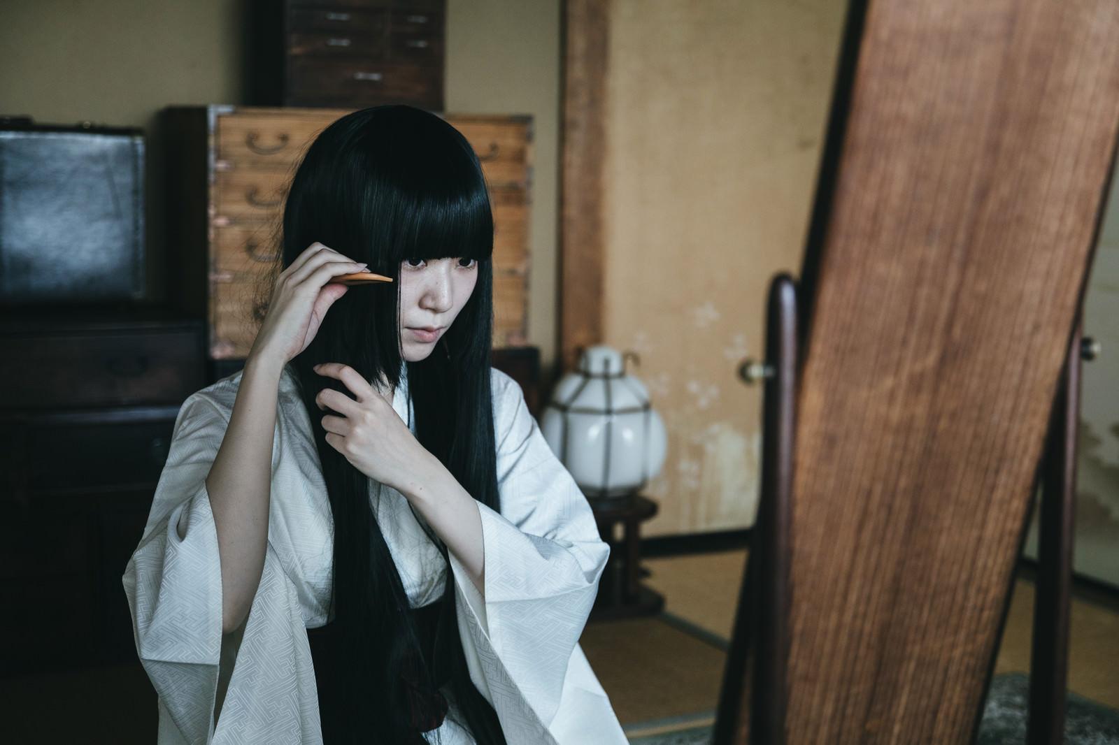 「鏡の前で髪をとかす女性(和室)」の写真[モデル:緋真煉]