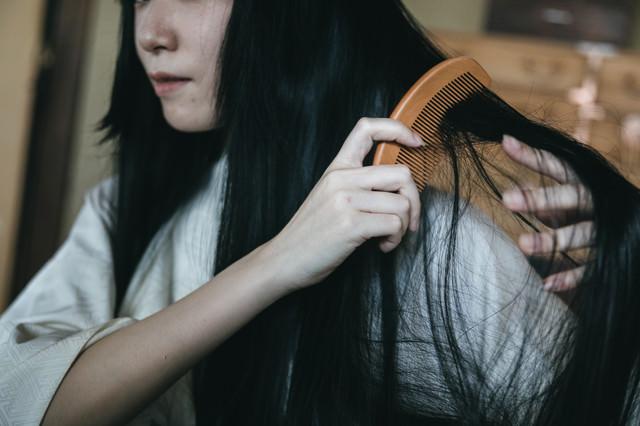 絡まった髪を櫛で無理やりとおす女性の写真