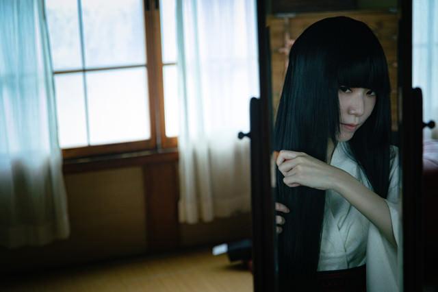 鏡を見ながら長い黒髪をとかす女性の写真
