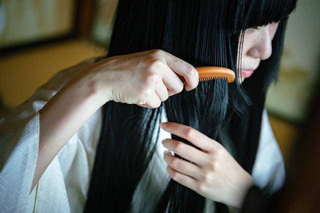 長い黒髪にくしをとおす女性の写真