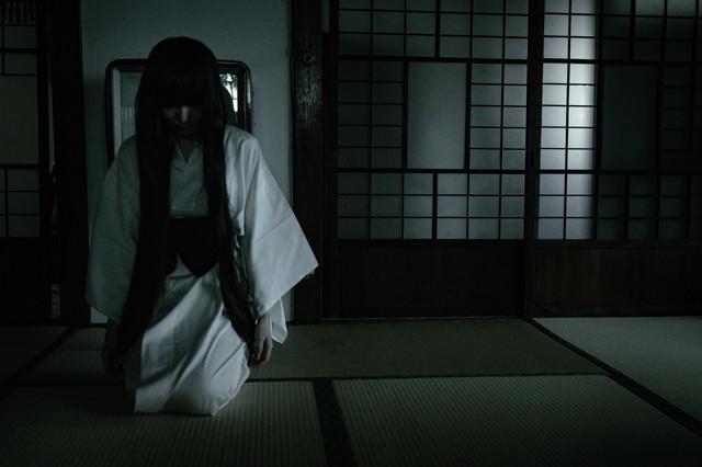 薄暗い畳のある和室と髪の長い白装束の女性の写真
