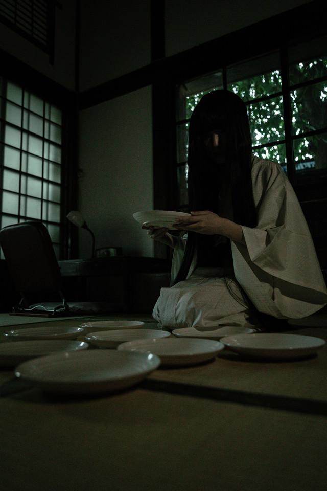 皿の枚数を数え始める黒髪女性の写真
