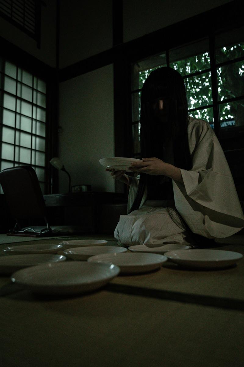 「皿の枚数を数え始める黒髪女性」の写真