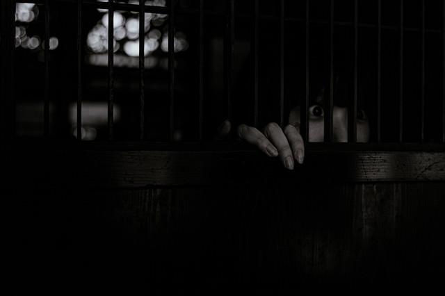 身を潜め惨劇を目の当たりにする女性の様子の写真