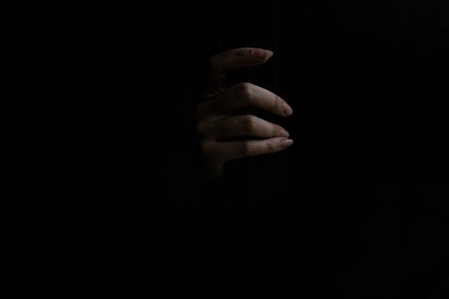 暗闇からスゥーっと女性の手がの写真