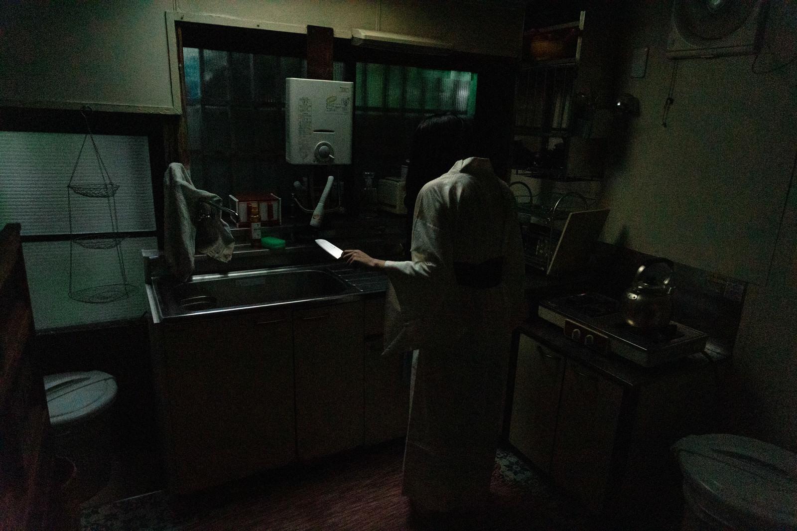 「包丁を片手に立ちすくむキッチンの幽霊」の写真[モデル:緋真煉]