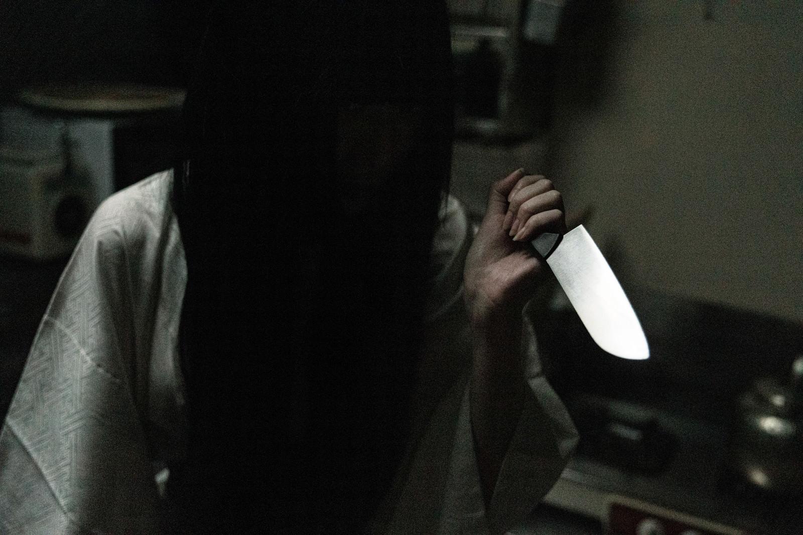 「包丁を握りしめるシャイな女性」の写真[モデル:緋真煉]