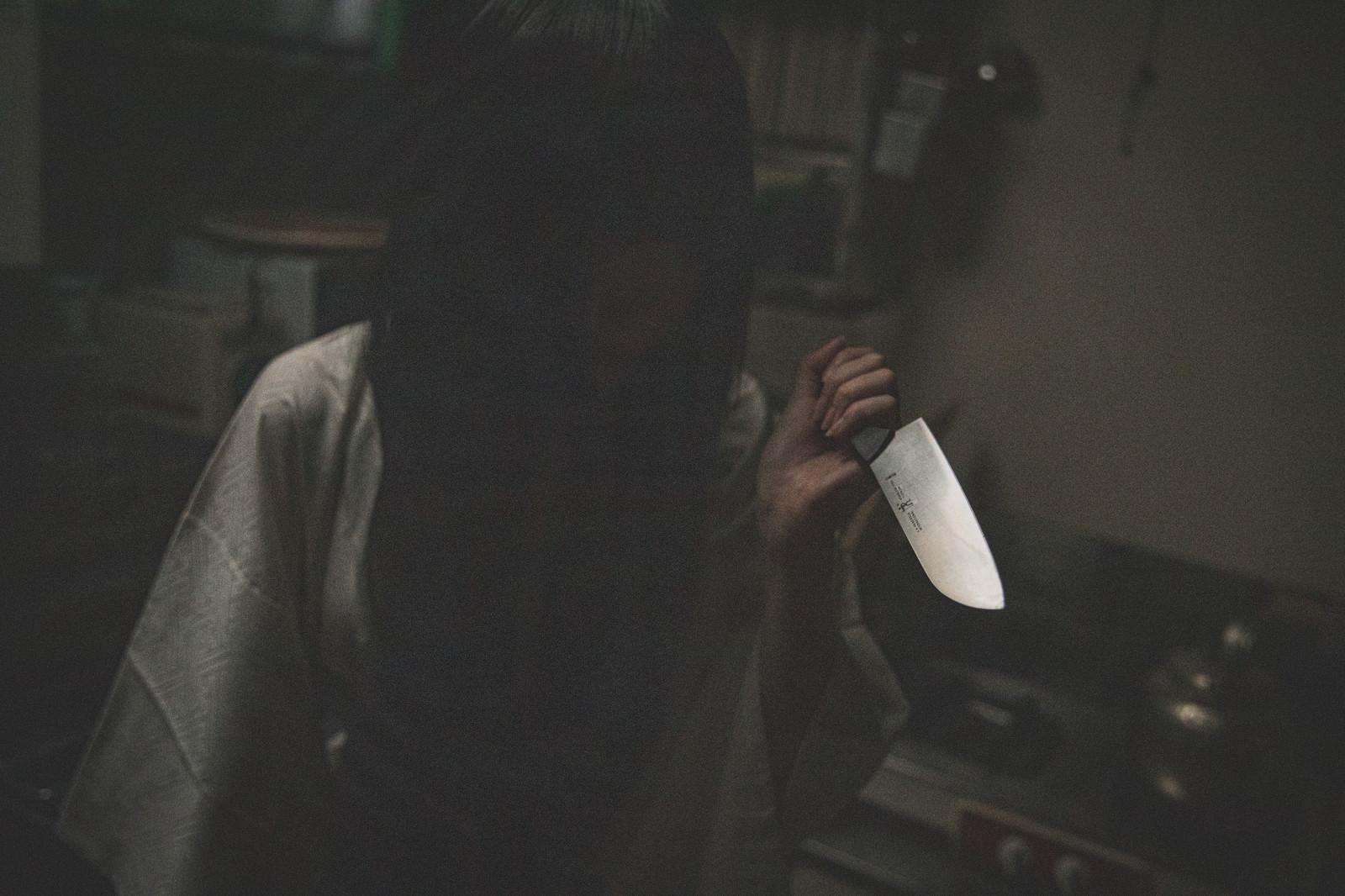「暗がりで包丁を持つ黒髪の女性」の写真[モデル:緋真煉]