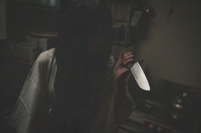 暗がりで包丁を持つ黒髪の女性の写真