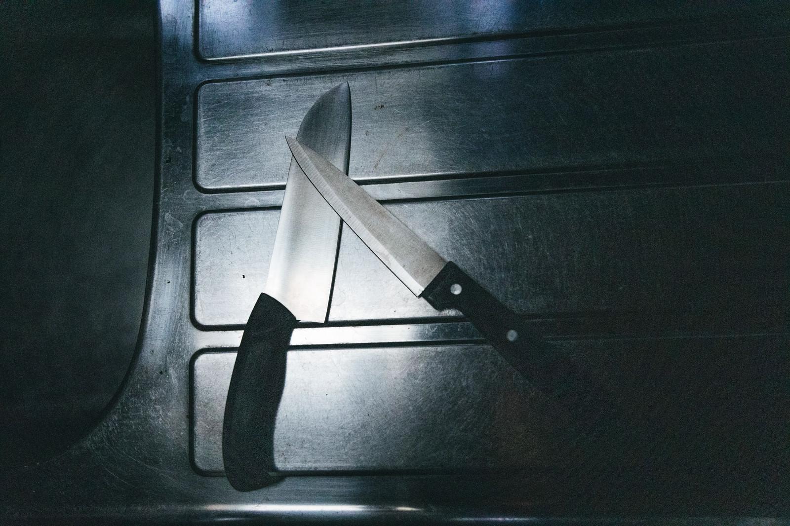 「キッチンのシンク横に置かれた包丁二本」の写真