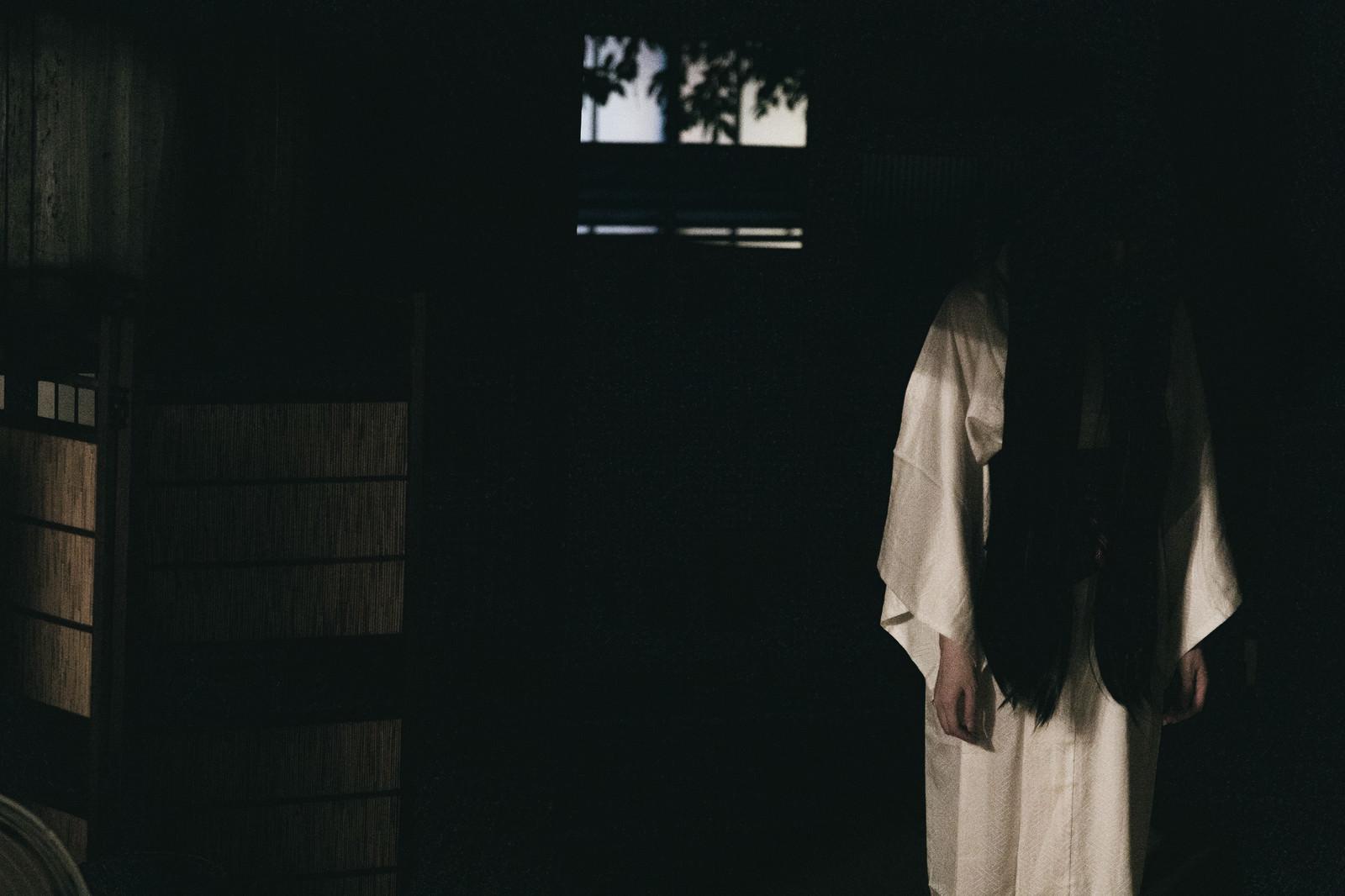 「暗闇の中から下を向いた女性の霊」の写真[モデル:緋真煉]