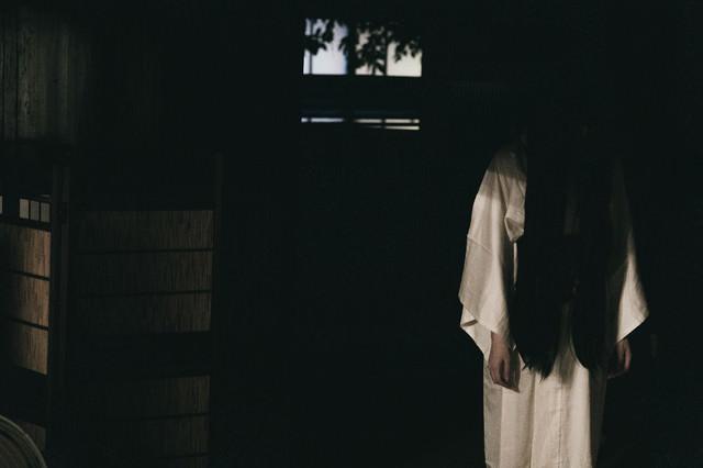 暗闇の中から下を向いた女性の霊の写真