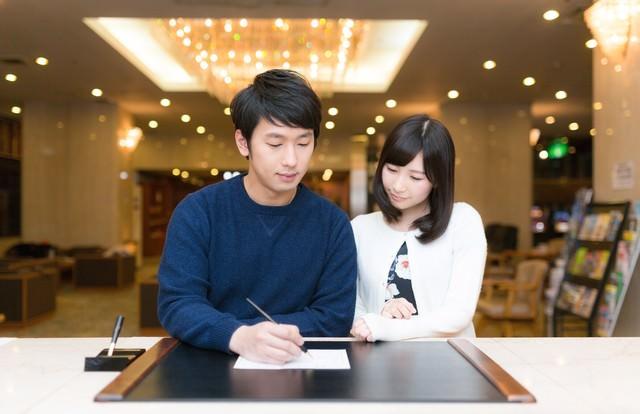 ホテルに到着しチェックインをするカップルの写真