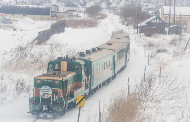 雪の中を走る運輸車両の写真