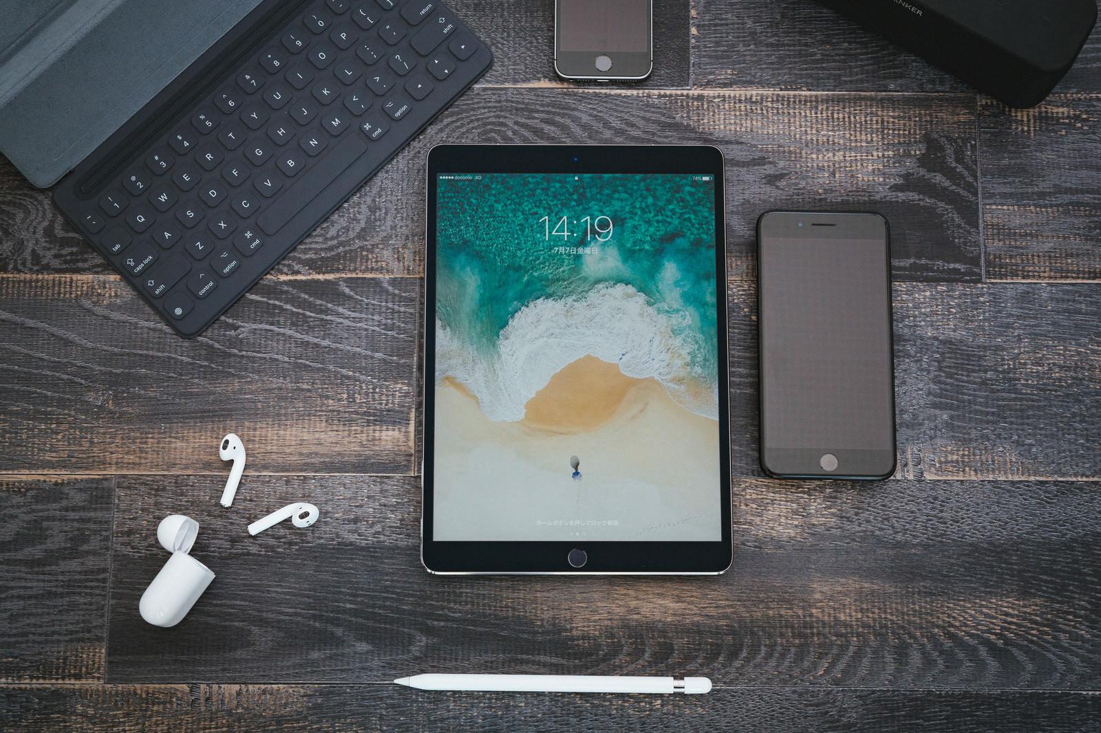 「木目調の床に置かれたスマートフォンやタブレット」の写真