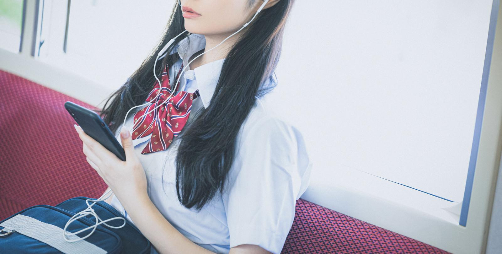 「通学中にスマホで音楽を聴く女子高生(有線)」の写真[モデル:石投げて美奈代]