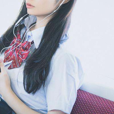 通学中にスマホで音楽を聴く女子高生(有線)の写真