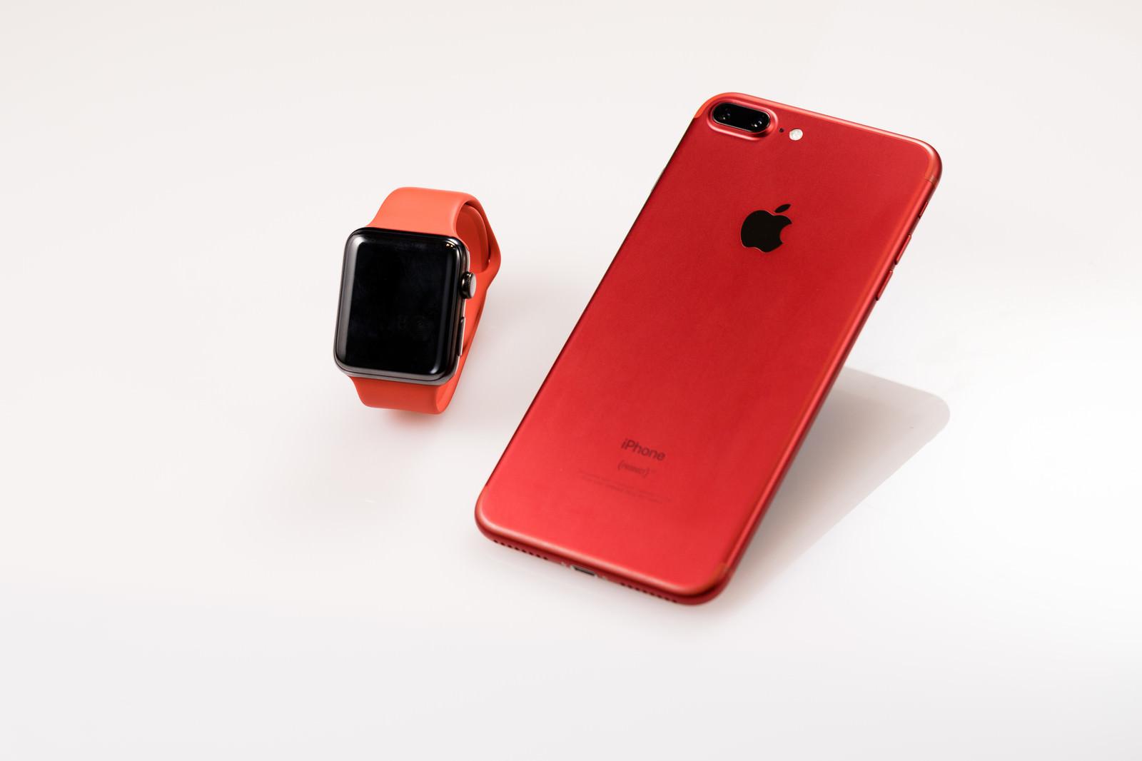 「赤いスマートフォンとスマートウォッチ」の写真